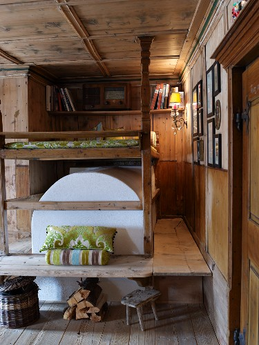 Bed above masonry stove in wood-panelled parlour