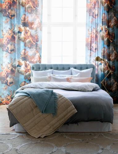 Doppelbett mit Bettwäsche und Decken in Pastelltönen, Vorhang mit Engelmotiven