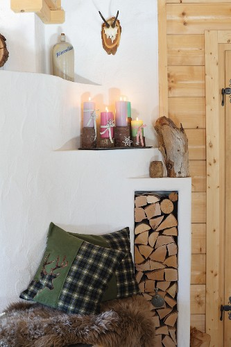 Masonry fireplace with colourful pillar candles on wooden stands