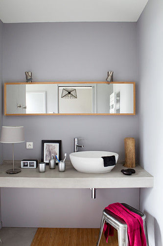 Basin and accessories on washstand below mirrored cabinet in bathroom