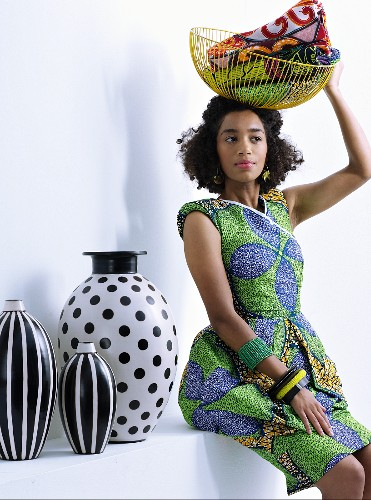 Young woman wearing ethnic dress holding wire basket next to black and white vases