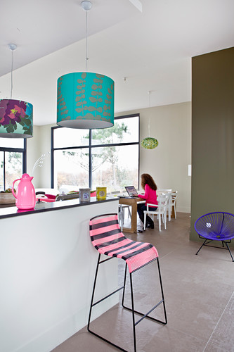 Woman working on laptop in open-plan kitchen-dining room with colourful accessories