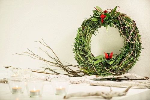 Hand-made wreath of herbs decorated with chillies and tealight holders