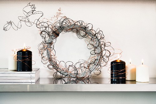 Decorative wreath hand-made from copper wire between lit, black and white candles