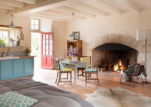 Open fire in large fireplace, kitchen table and double bed in open-plan interior