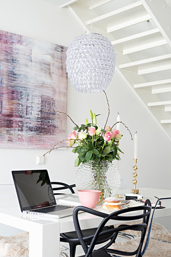 Vase of roses and laptop on white table and black chair in front of modern painting with pink accents in dining area