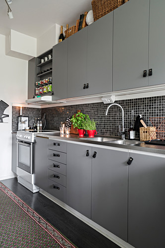 Kitchen with leather handles on grey cupboards and drawers