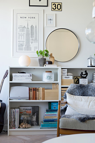 Pictures and mirror on wall above shelves full of books and ornaments