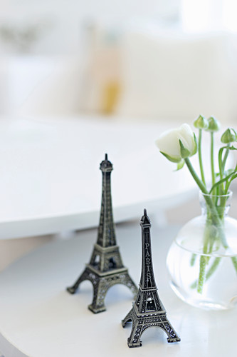 Two small Eiffel towers next to vase of ranunculus
