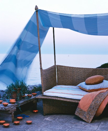 Couch below canopy surrounded by candles and with sea view
