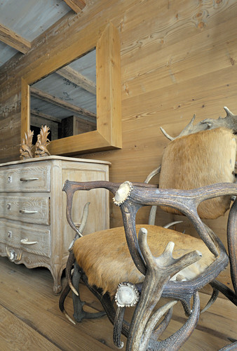 Armchair made from antlers and fur next to chest of drawers against wooden wall