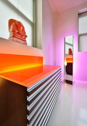 Indirect, orange and pink lighting around mirror and chest of drawers