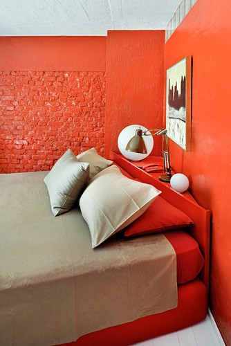 Double bed in bedroom with red-painted walls