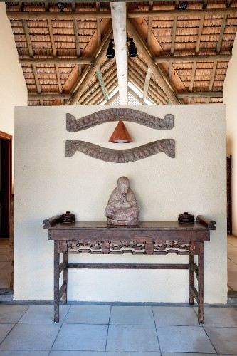 Buddha statue on antique wooden table against partition wall