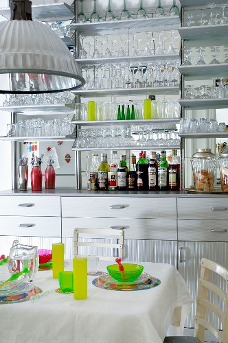 Kitchen counter with mirrored splashback and many glasses on wall-mounted shelves behind colourful place settings on white table