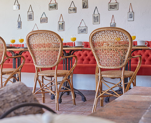 Red bench and vintage cane chairs in dining room