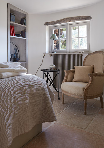 Antique armchair with cushion, side table and fitted shelving in rustic bedroom