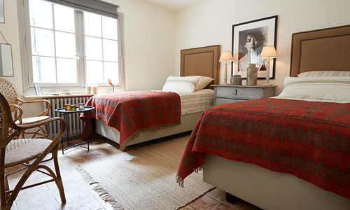 Twin beds with tall headboards in rustic bedroom