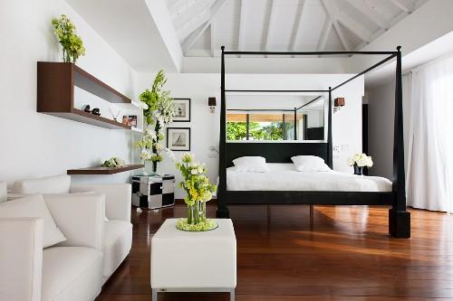 Black-framed bed with white bed linen, leather furniture and flower arrangements in elegant bedroom