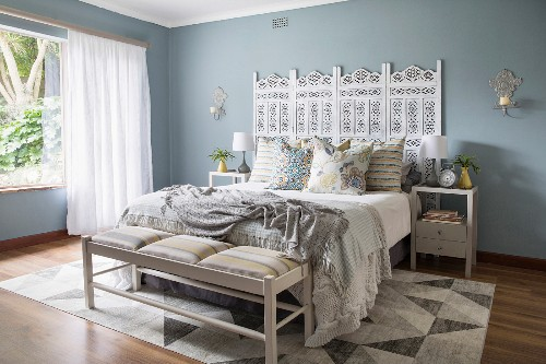 Double bed with ornate headboard in bedroom