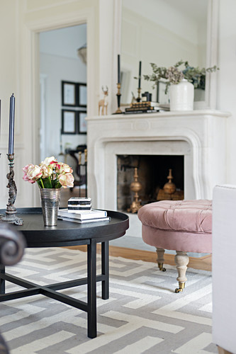Round coffee table on rug with graphic pattern in front of fireplace