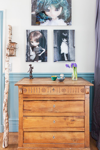 Photos of dolls on wall above old wooden chest of drawers
