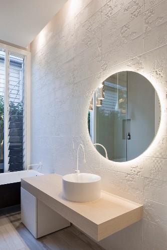 Round mirror on white structured wall tiles in minimalist bathroom