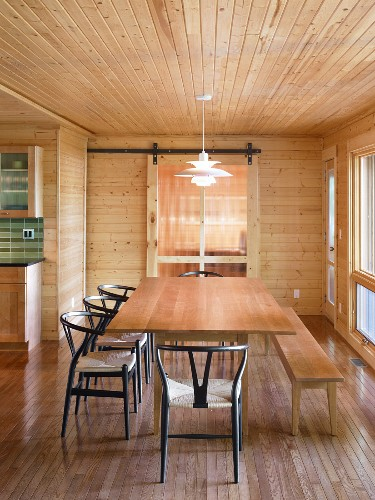Wooden table with bench and black chairs in renovated, wood-clad house