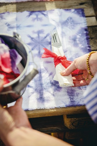 Woman's hands setting table with purple batik placements and cutlery