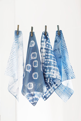 Old handkerchiefs hand-dyed using Shibori technique hung from line