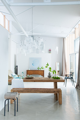 Modern dining room with concrete floor and wooden furniture in loft apartment