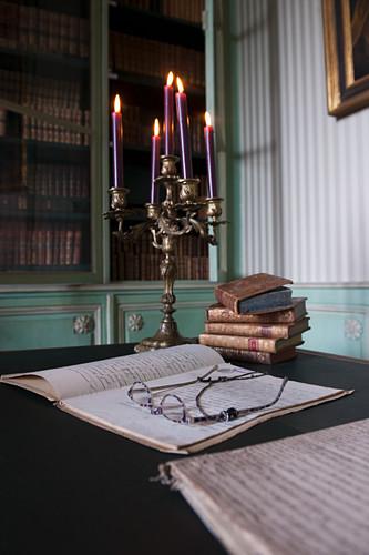 Reading glasses on open, handwritten notebook in front of candelabra