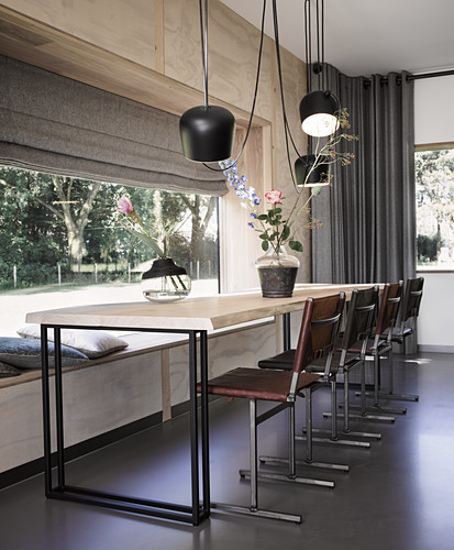 Long dining table, chairs and pendant lamps next to panoramic window