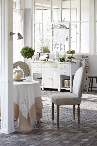 Round table and upholstered chair in front of white kitchen sink and period interior window