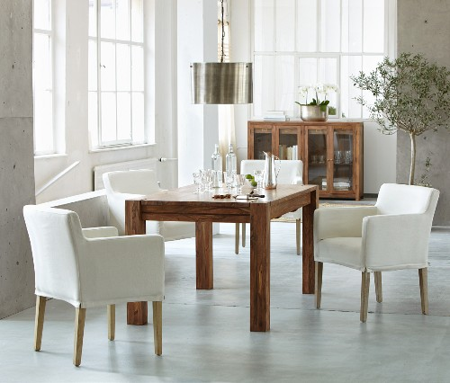 White armchairs and solid exotic-wood table in bright interior with industrial glazing