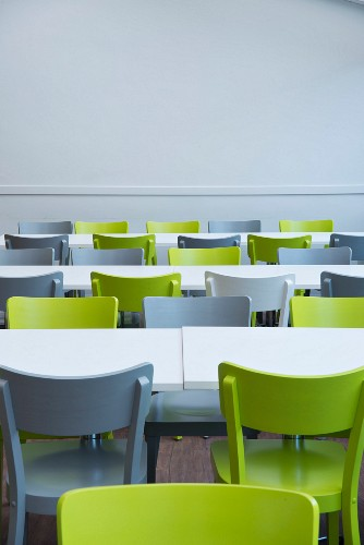 Green and grey chairs at white tables in canteen