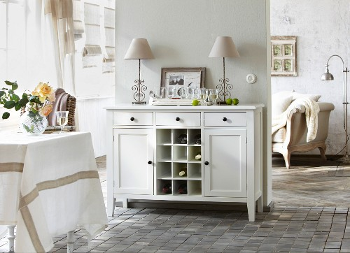White dresser against partition wall with living room in background