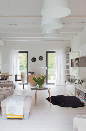 Wood-beamed ceiling and white floor in bright living room