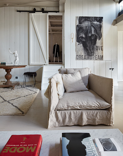 Loose-covered armchair against wood-clad wall and doorway leading to bedroom in loft apartment