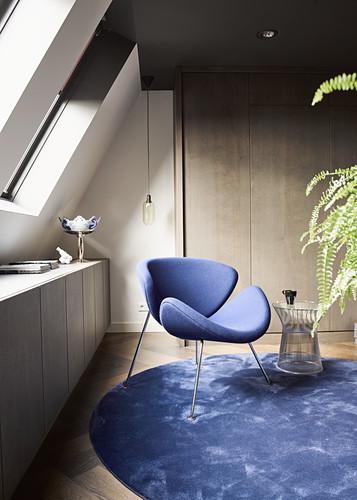 Blue designer chair on round blue rug below skylights