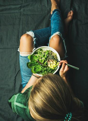 Person isst vegane grüne Power-Bowl mit Spinat, Rucola und Avocado