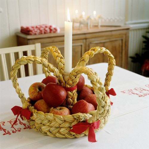Crown woven from straw holding apples and a single candle