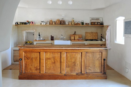 Wooden island counter in traditional kitchen in trullo