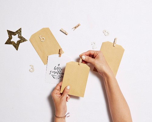 Hands stick wooden clips to small paper bags
