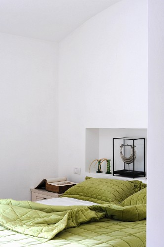 Bed with green covers, antiquarian book on bedside cabinet and objets d'art in niche at head of bed
