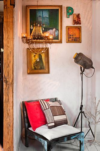 Various cushions on vintage chair below chandelier