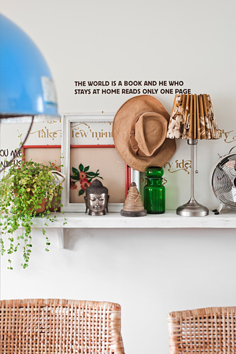 Houseplants, ornaments and table lamps on wall-mounted shelf