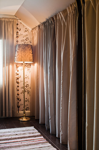 Floor-length curtains screening dressing room and standard lamp in bedroom