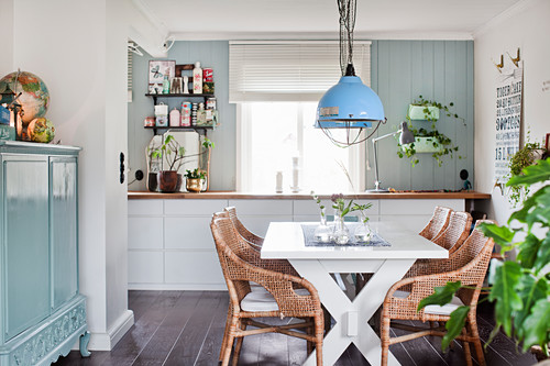 White dining table, rattan chairs and cabinet painted pale blue in open-plan interior