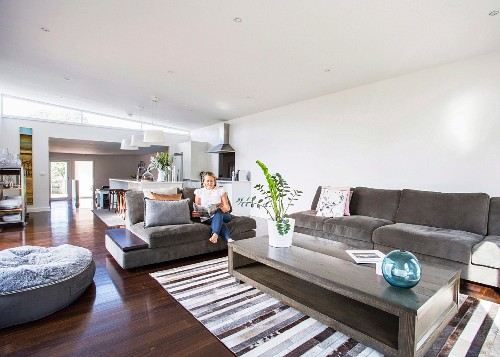 Open living area with upholstered furniture and matching coffee table, woman sitting on sofa